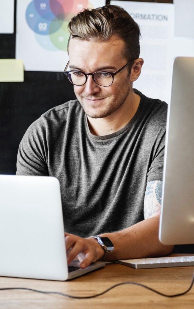 En man arbetar med en hemsida i WordPress vid datorer