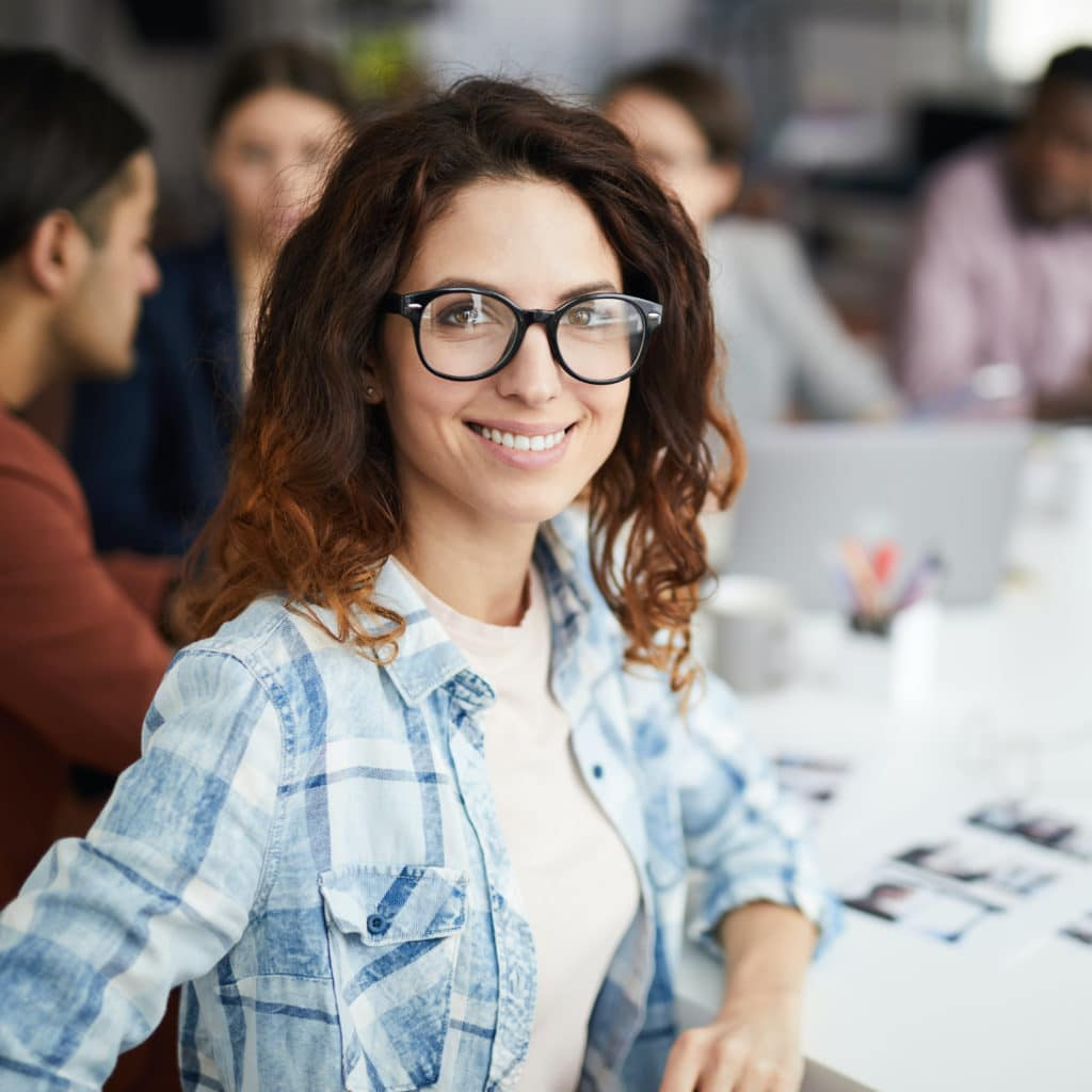 Leende kvinna med glasögon i förgrunden med kollegor på ett företag i bakgrunden