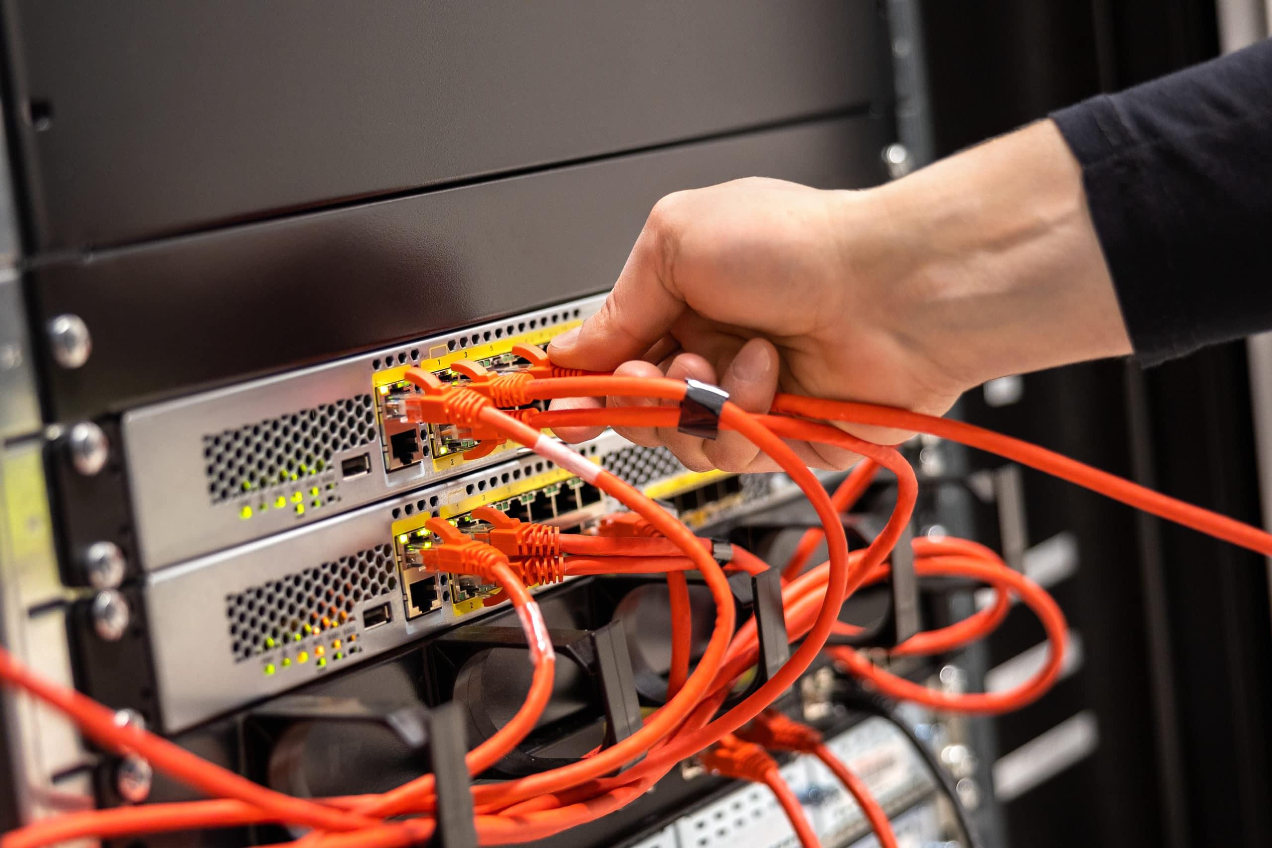 Närbild på en hand som kopplar in sladdar på nätverksenhet i datorhall