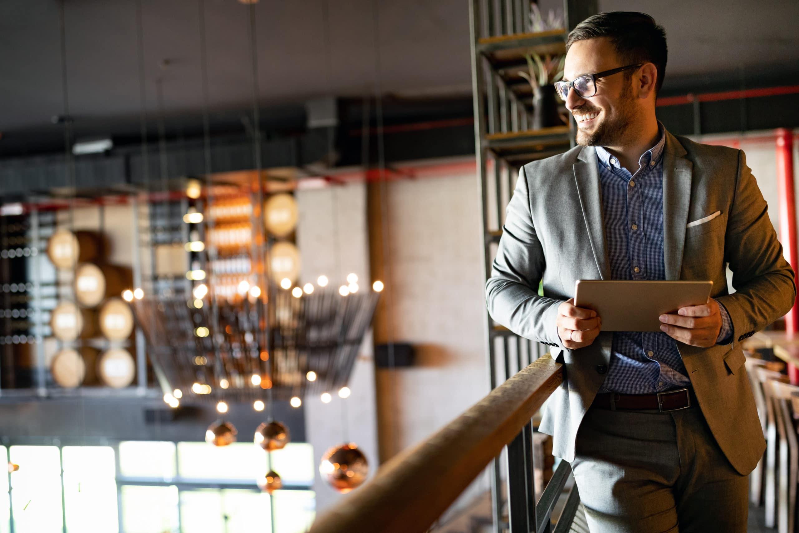 En man står och uppe på en öppen övervåning och tittar ut över interiören på någon form av företagslokal. Han har kostym och håller i en surfplatta och ser nöjd ut.