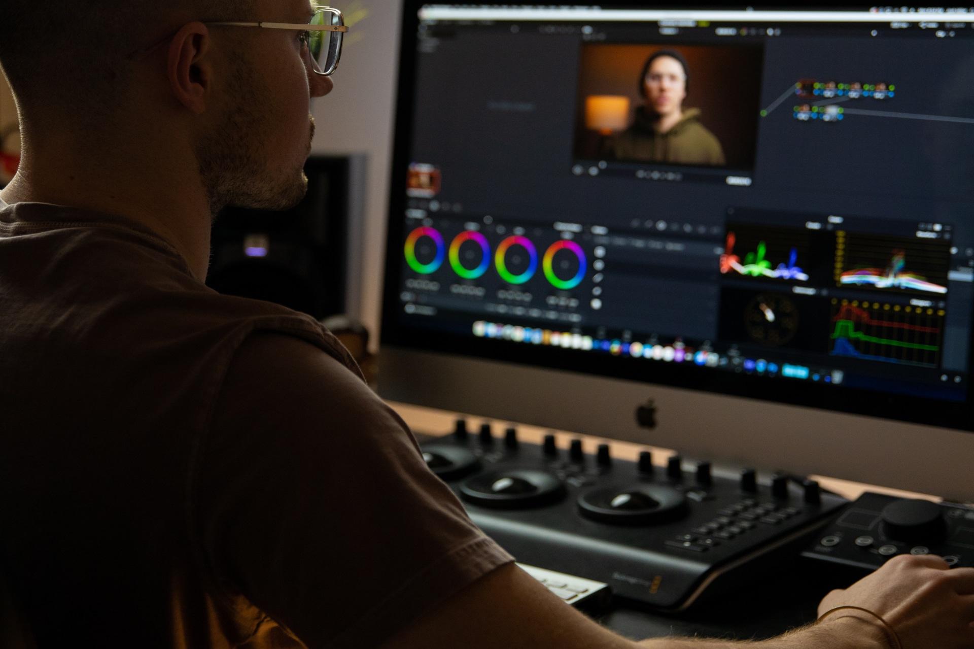 En man arbetar med videoredigering på dator i dämpad belysning