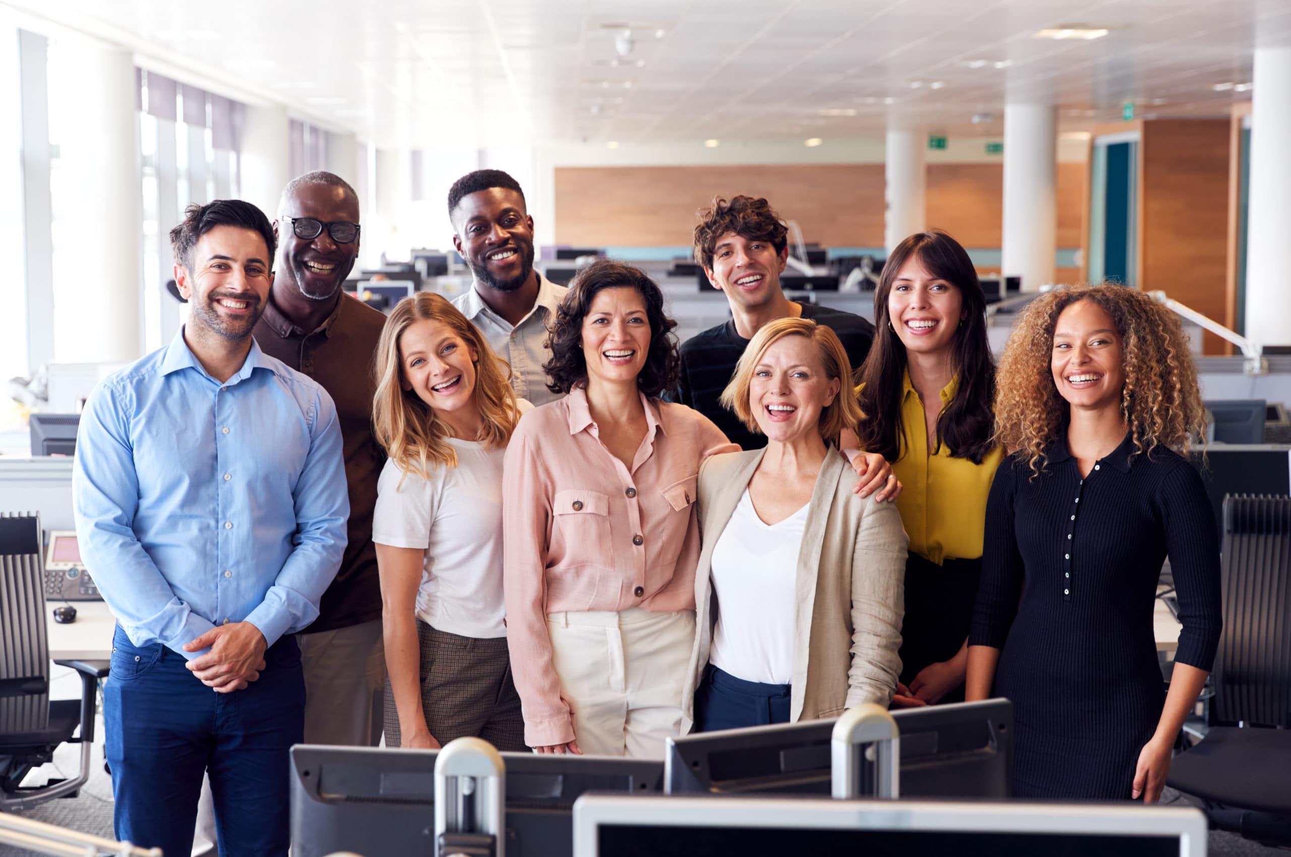 Arbetslag av olika kön och etnicitet står samlade i grupp framför kamera i kontorsmiljö