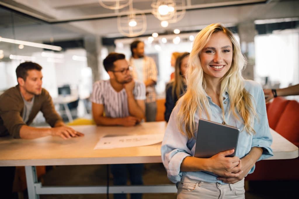 Tjej med blont hår står framför sina kollegor på kontor. Hon håller i en surfplatta och ser glad ut.