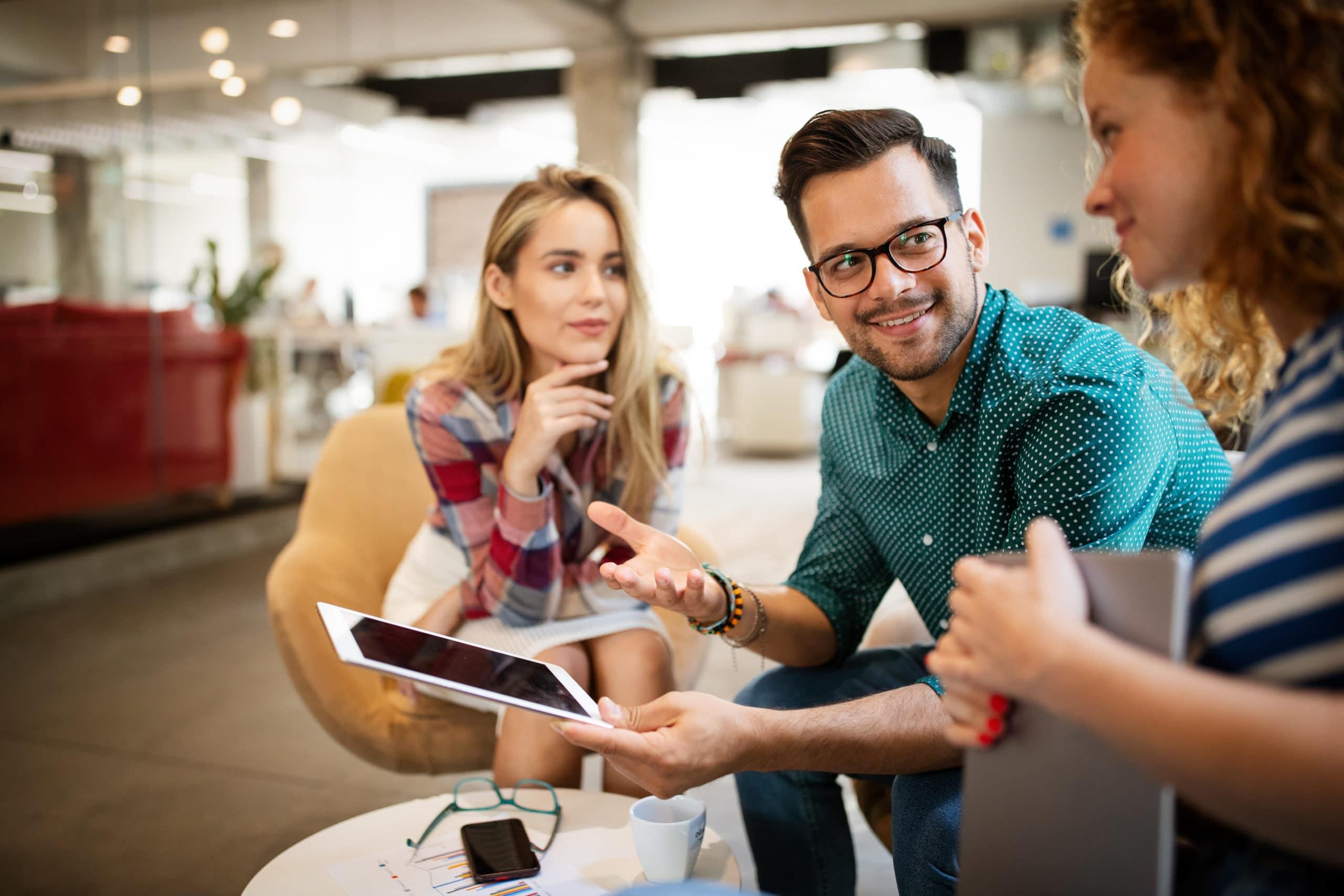 En glad man diskuterar något som finns på en surfplatta med två kvinnliga personer sittandes i kontorsmiljö.