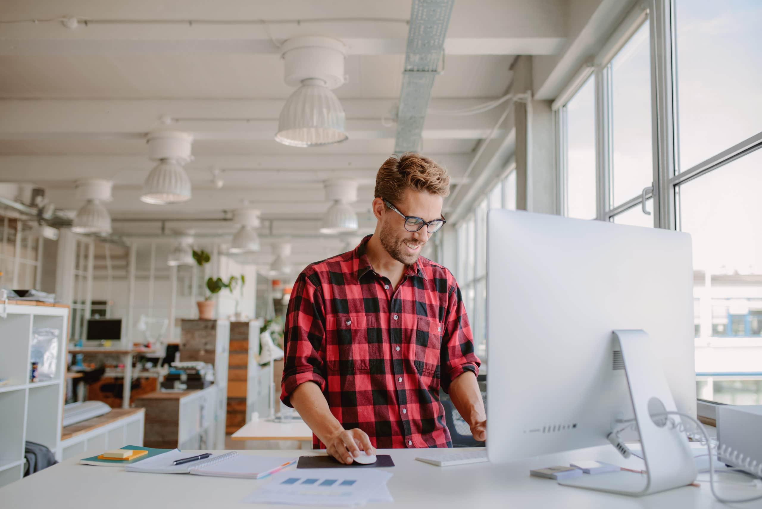 Ung glad man ser glad ut och arbetar på dator vid skrivbord på kontor