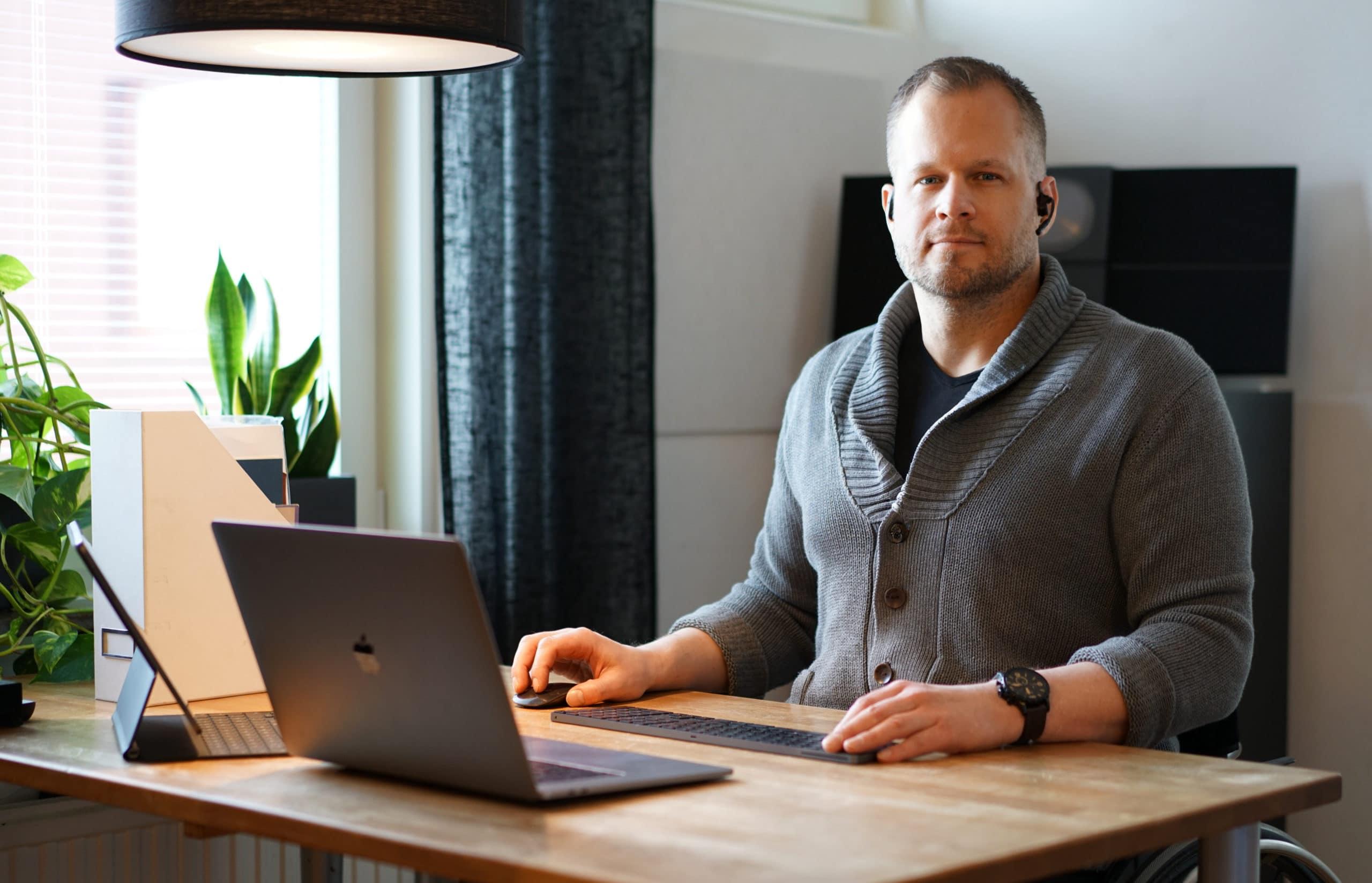 En man sitter vid skrivbord framöver en bärbar dator. På ena örat hänger ett headset för samtal