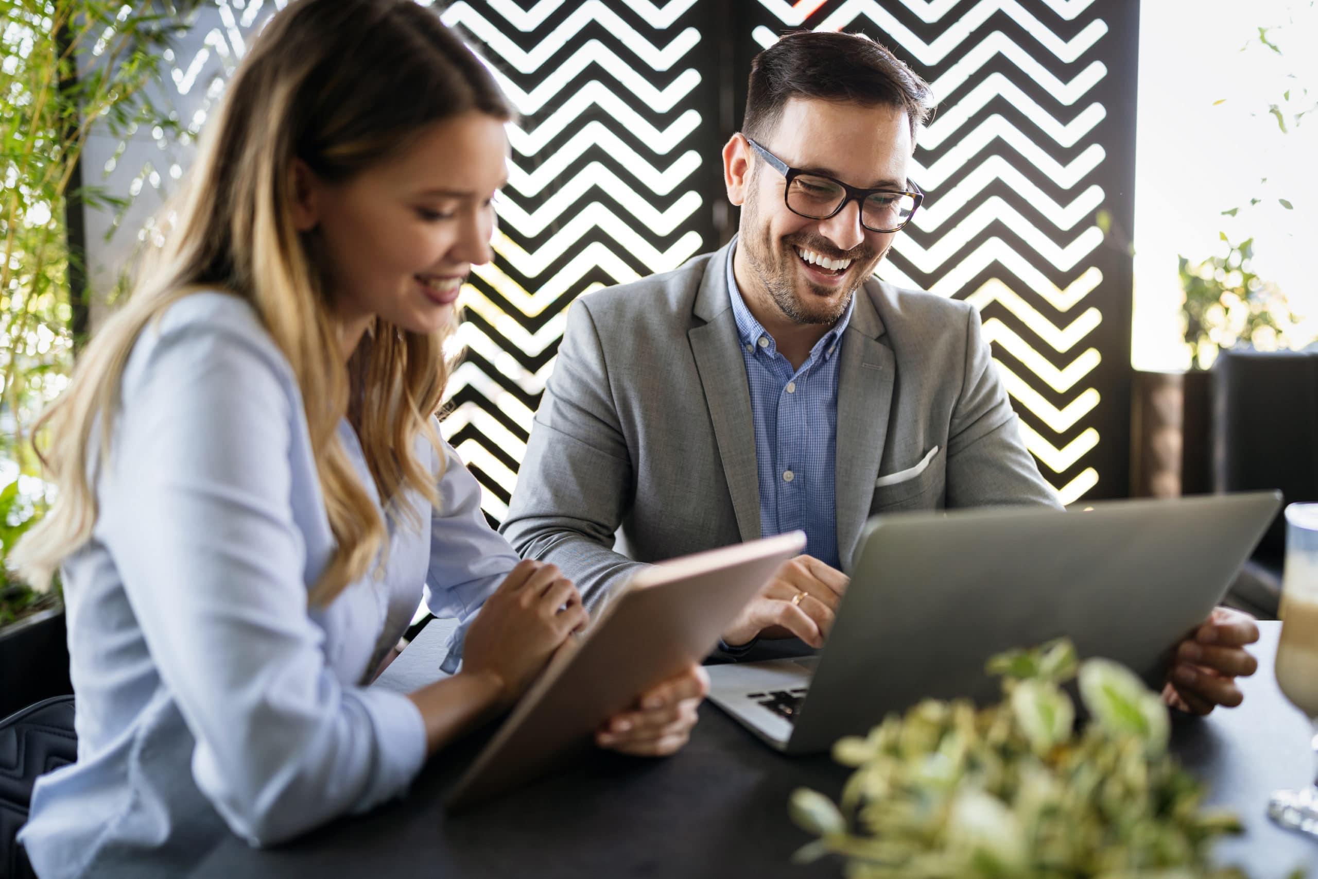 Två kollegor, man och kvinna arbetar glatt vid dator och surfplatta på kontor