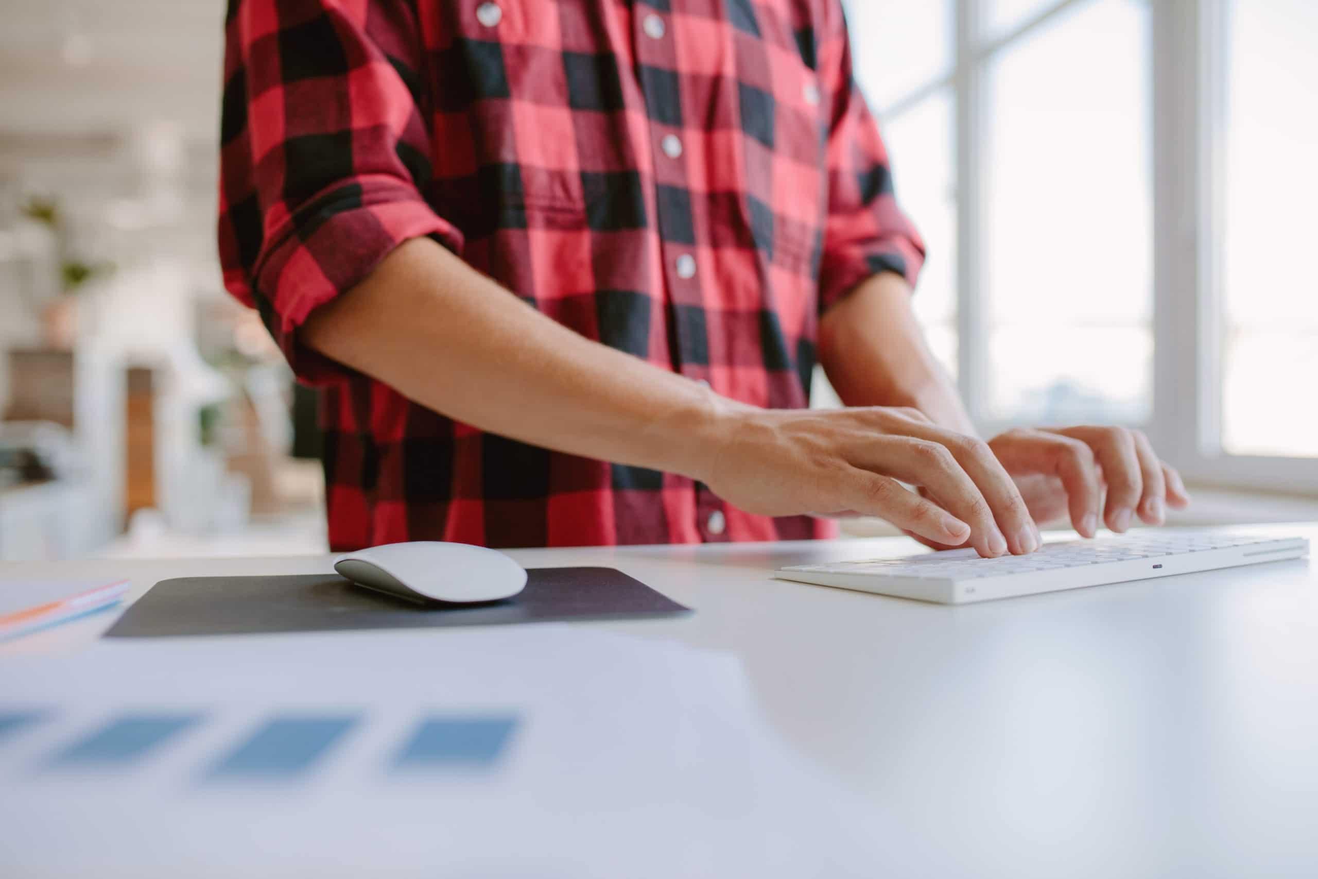 Händer skriver på tangentbord i kontorsmiljö