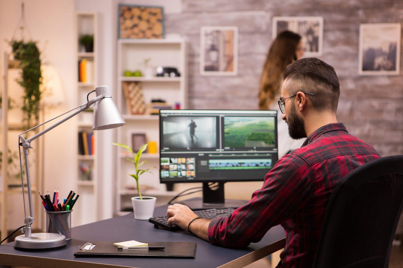 En man sedd bakifrån sitter och arbetar med videoredigering på dator i kontorsmiljö