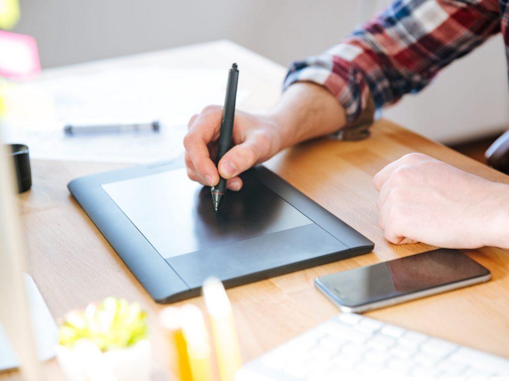En hand håller i en penna som ritar på en digital ritplatta.