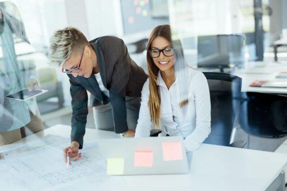 Två tjejer samarbetar med anteckningslappar på skrivbord på kontor