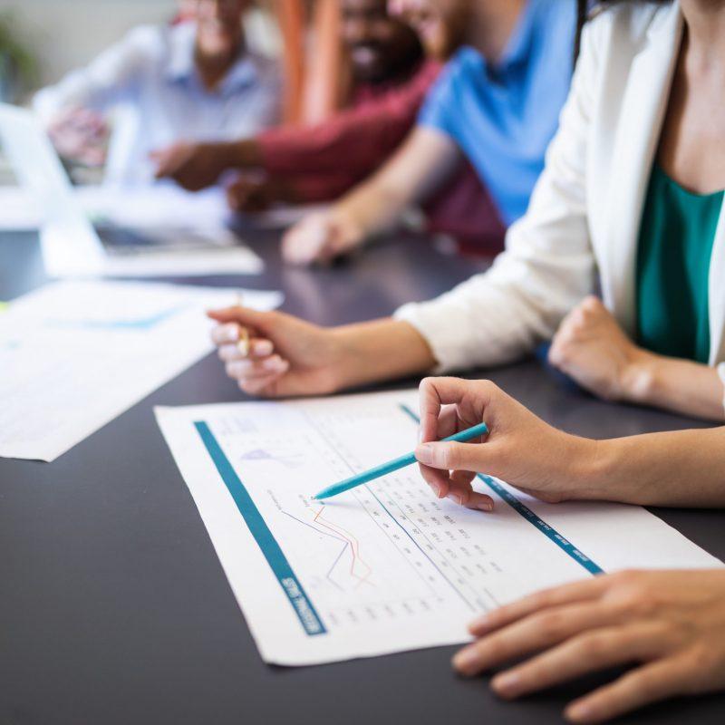 Flertalet händer syns i bild med penna pekandes på statistik på papper.
