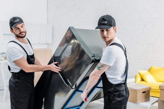 Två flyttarbetare bär ett kylskåp i rostfritt stål