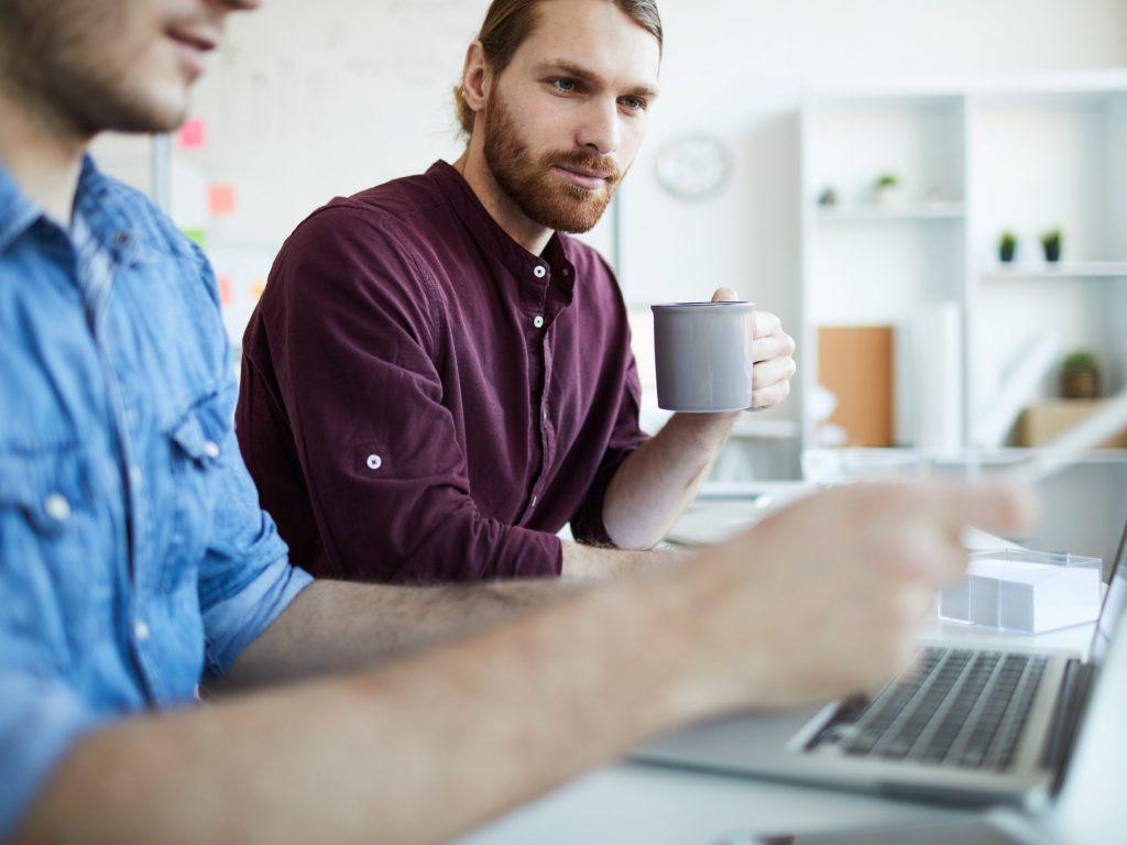 Två kollegor arbetar tillsammans med något projekt på en dator i kontor