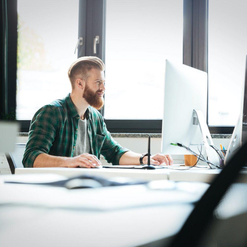 En webbutvecklare i skägg och brunt hår sitter och arbetar på kontor via dator och sköter om en hemsida åt en kund