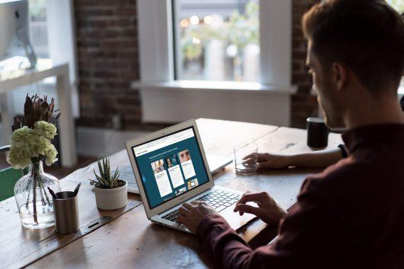 En man sitter med ryggtavla mot bild vid en bärbar dator. Belysningen är dunkel