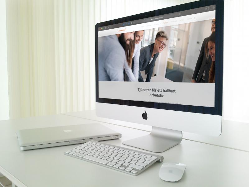 Datorskärm på vitt skrivbord visar hemsida från kundexemplet Arendra