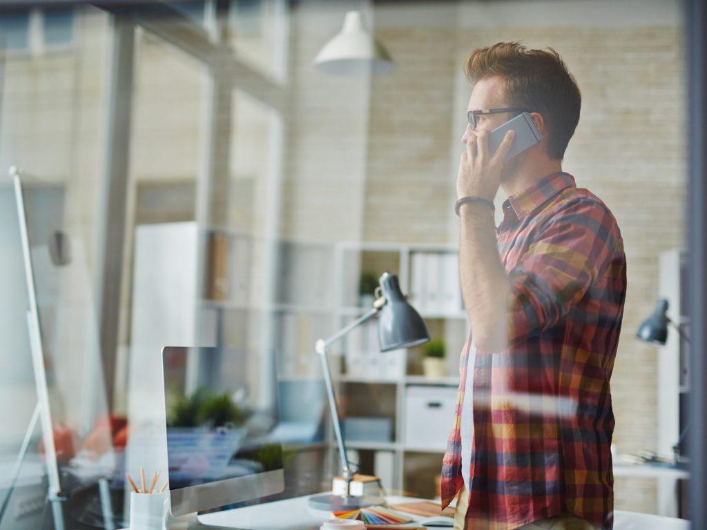 En ung man står bakom ett glasfönster inne på sitt kontor och pratar i telefon