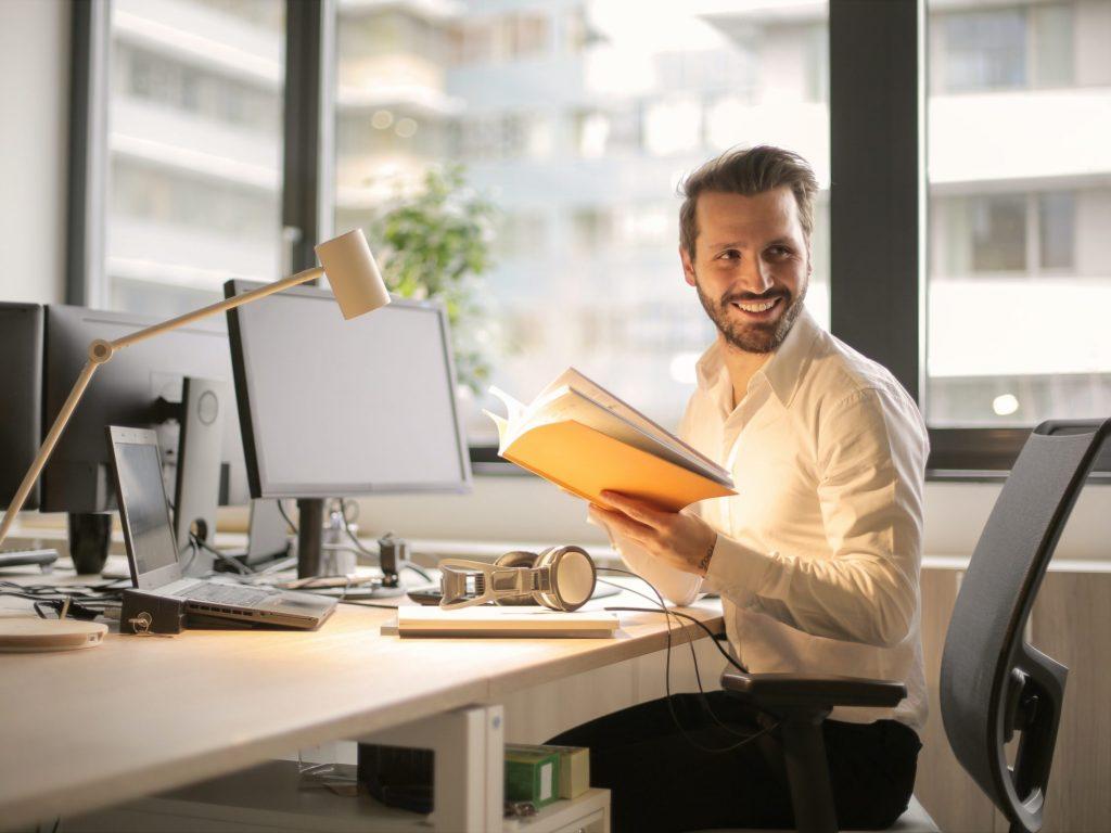 En glad person håller i en bok och sitter vid en skrivbordsdator i kontorsmiljö