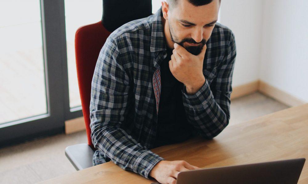 En man i skägg sitter framåtlutad över bärbar dator vid skrivbord och är fokuserad på något