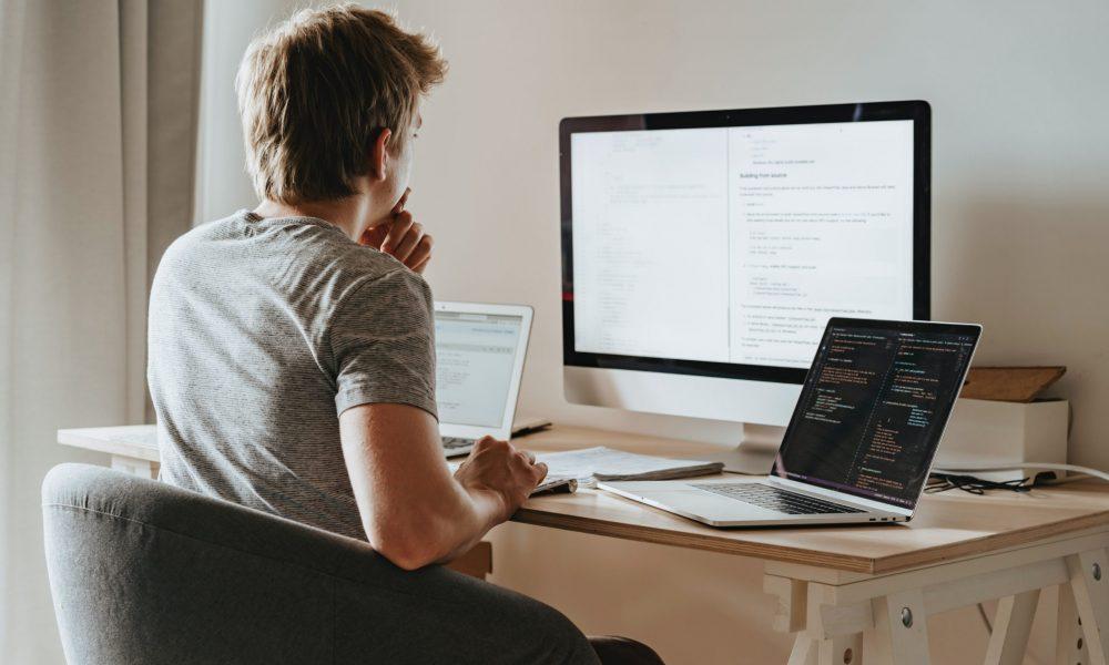 Ryggtavlan på en ung man som koncentrerat arbetar med något på en dator på kontor.