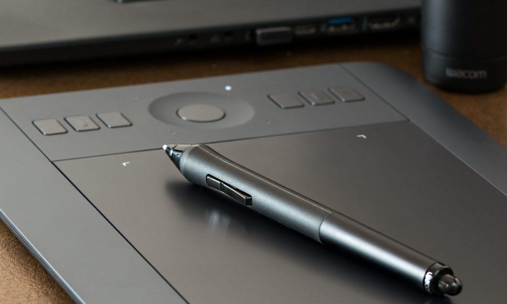 Svart digital ritplatta ligger på ett bord med en svart penna för digitala ritplattor ovanpå.
