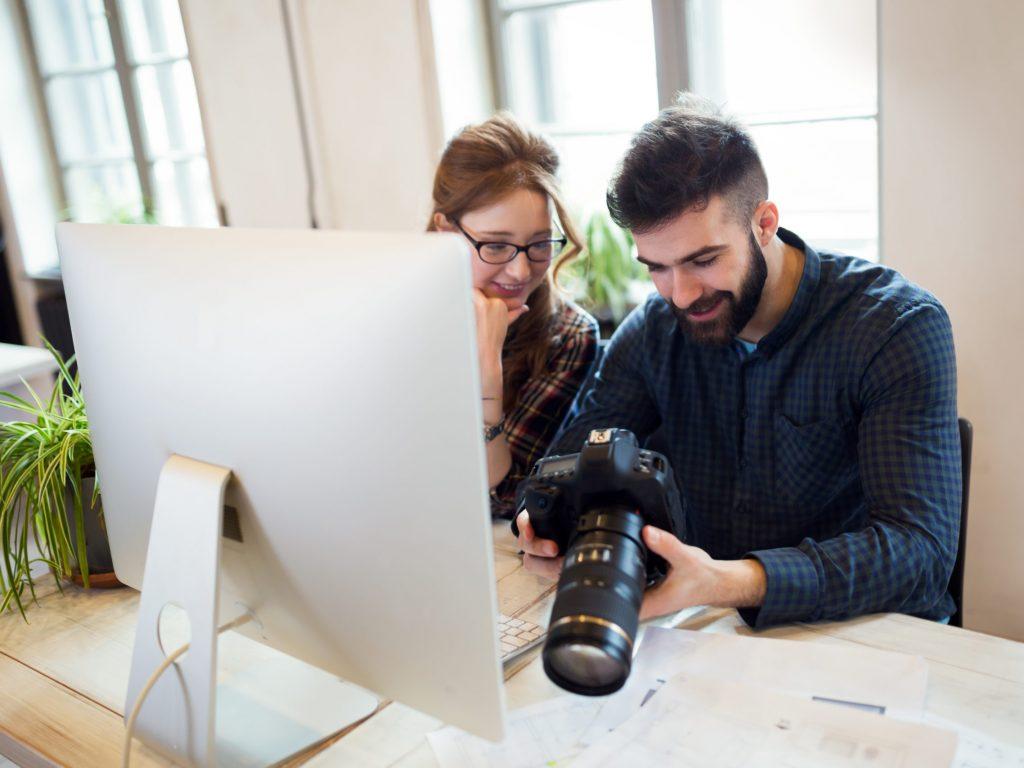 En man och kvinna tittar på foton på displayen på en systemkamera. Intill dem på bordet står en datorskärm. De sitter i kontorsmiljö