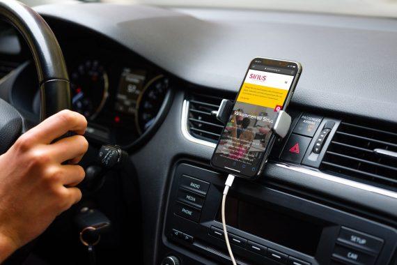 Hand på ratt i bild. En smartphone är monterad mot instrumentpanelen med en responsiv hemsida på displayen