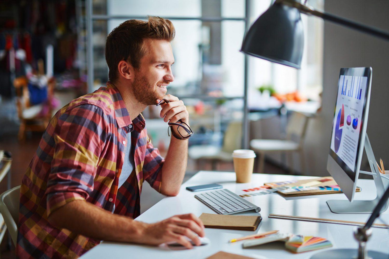 En glad ung manlig person sitter och arbetar vid dator. Han tittar på skärmen som visar någon form av statistik. Rummet är någon form av kontorsmiljö
